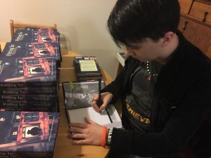 Photo of Artist Shannon Legler signing copies of Fitting In.