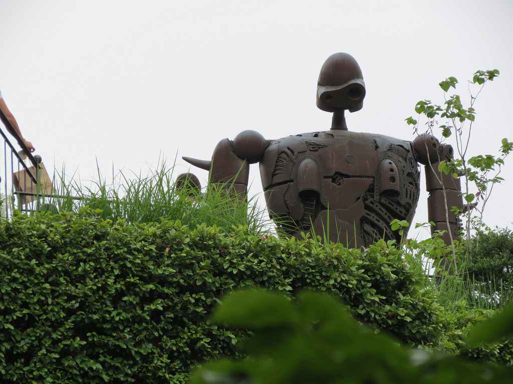 Robot towering over hedges