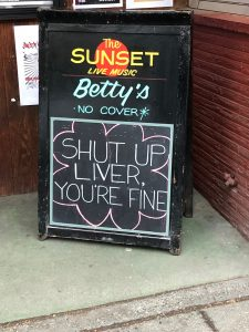 "Photo of sandwich board sign that reads ""The Sunset, Live Music, Betty's, No Cover."" Written in chalk at bottom is ""Shut Up Liver, You're Fine."""