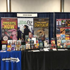 Convention table displaying books from Matt Youngmark and DefCon One
