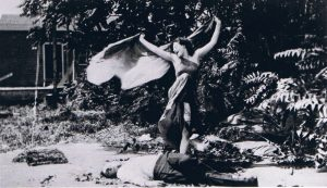 Still from the 1913 film The Vampire, picturing a female vampire standing over a man who she has defeated