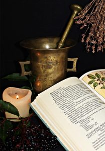 Open book, candle, and copper mixing vessel