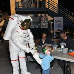 Child wearing goggles interacting with an astronaut in a full suit