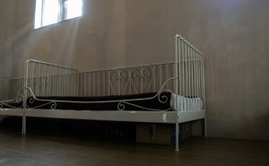 Simple empty bed with white metal railing on three sides
