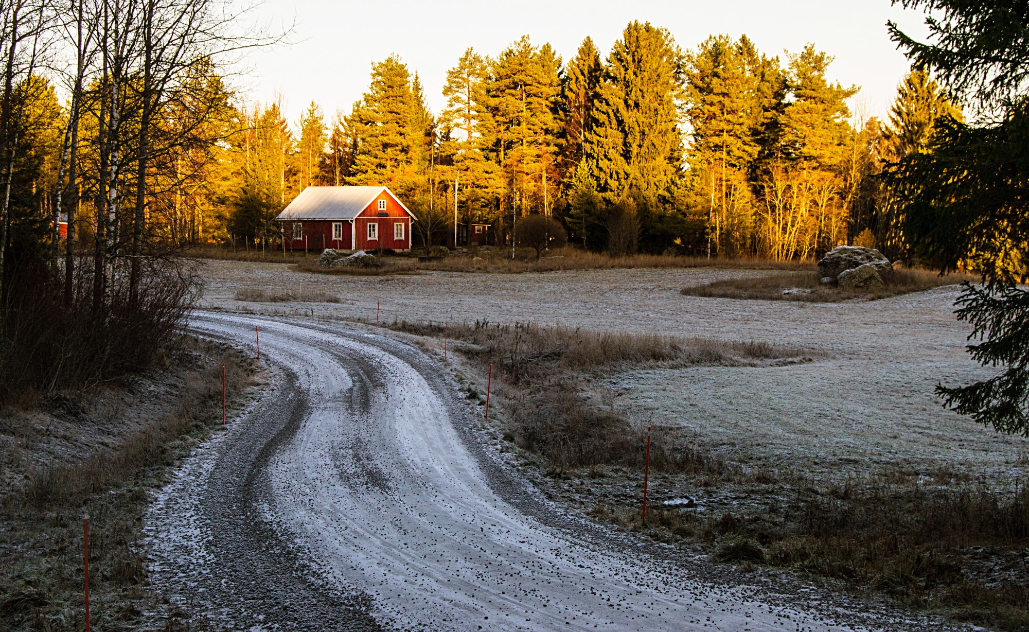 Red farmhouse in the distance, with a snowy path leading toward it