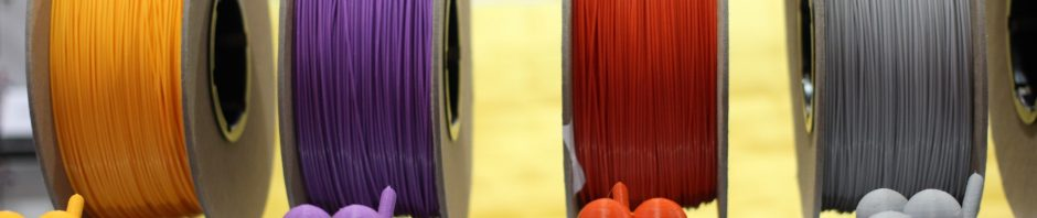 Spools of 3d printing filament in gold, purple, red, and gray, with small 3D printed balloon animals in front of each