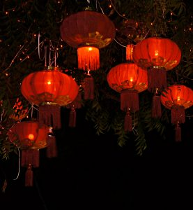 Red lanterns lit by candles against a dark background